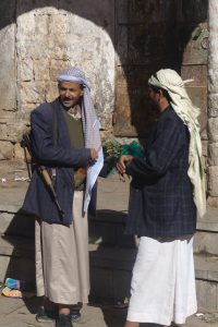 Two Yemeni men chatting and listening to each other.